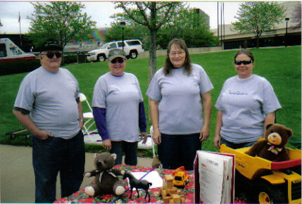 John, Judy, Carol, and Julie collecting toys in front of Bramlage Coliseum